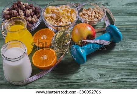 The concept of a healthy lifestyle. Cereals and fruit - diet and breakfast. Cornflakes, orange juice, yogurt, nuts, honey, tangerines, apple, dumbbell  and measuring tape on rustic wooden table.