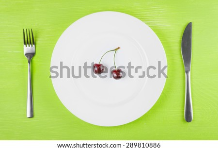 The concept of a healthy lifestyle, diet, weight loss, anti-obesity, healthy diet, raw food diet, vegetarianism, veganism. Two ripe cherries on a white plate, knife and fork, top view, closeup - stock photo
