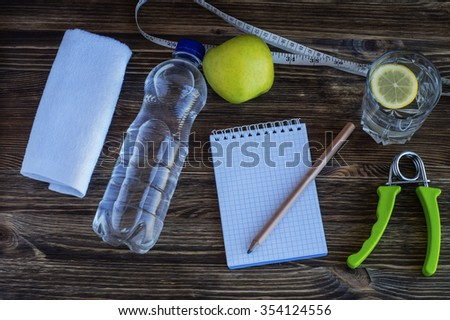 The concept of a healthy lifestyle. Workout and fitness dieting copy space diary. Apple, water, expander hand, and measuring tape on a wooden table. - stock photo