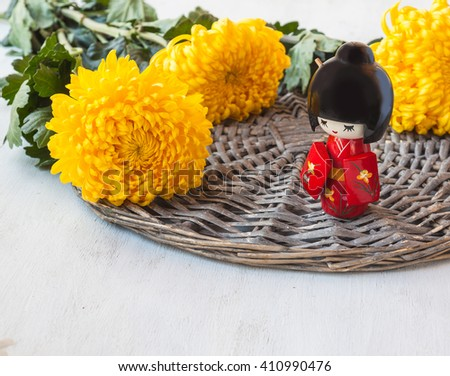 The concept of a Japanese holiday chrysanthemums  of the ninth lunar month of the traditional Japanese doll Kokeshi (mass production) - stock photo