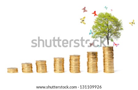 The concept of a successful business, butterflies around a tree on a coins mountain - stock photo