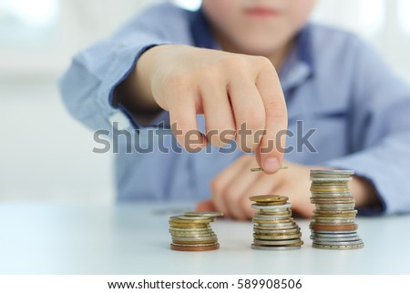 The concept of children's economic education. Young boy build a tower by coins.