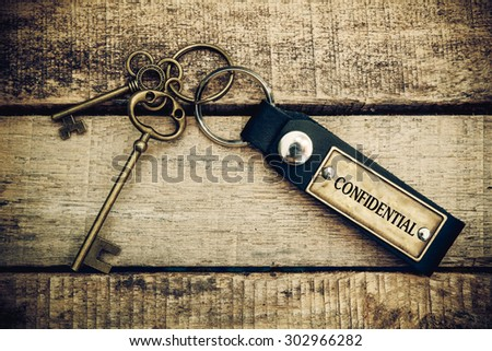 The concept of 'confidential' is translated by key and silver key chain - stock photo