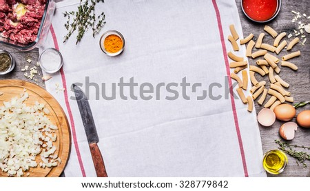 The concept of cooking raw minced  beef egg chopped onion knife seasoning paste tomato sauce on a white napkin on wooden background top view - stock photo