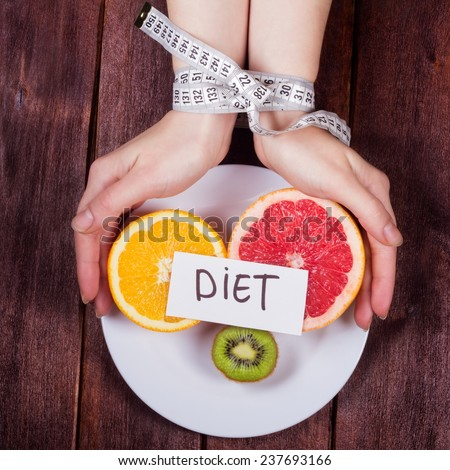 The concept of eating disorders: bulimia, anorexia, diet fads. Women's hands tied centimeter. Girl's hands with a plate and fruit. Fruit diet. Low-fat diet. - stock photo