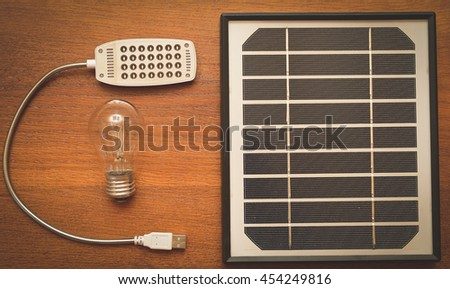 the concept of green energy. Little solar panel and an incandescent lamp with a lamp of the diodes - stock photo