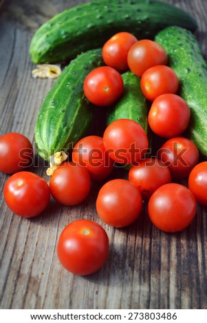 The concept of healthy eating with organic cucumber and cherry tomatoes on wooden table