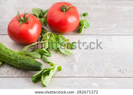 The concept of healthy eating with organic cucumber and tomatoes on wooden table
