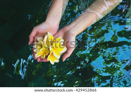 The concept of healthy way of life and purity. Wellness young beautiful girl holding tropical flowers frangipani on clean water in the pool. - stock photo