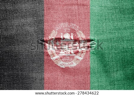 The concept of national flag on denim material with hole: Afghanistan  - stock photo