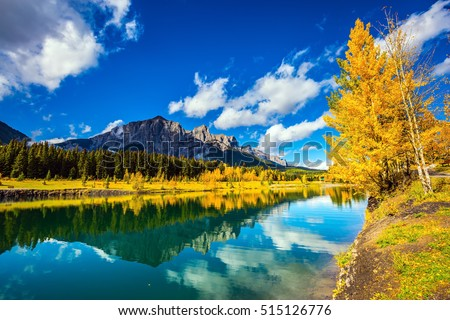The concept of recreational tourism. Canmore, near Banff National Park. Jagged mountains and red-orange trees are reflected in smooth water of the lake
