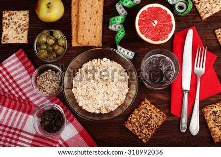 The concept of the classic diet breakfast with oatmeal, grapefruit, useful loaves, nuts and grapes on dark wooden surface. Vegan concept - stock photo