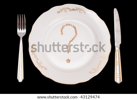 """The conceptual image on a theme """"What to eat?"""". A set of tablewares on a black background. On a plate the sign on a question from lentil is laid out. - stock photo"""