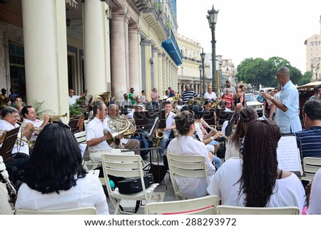 The conductor with brass band in Havana/One of the regular free performings of the brass band on the streets of Havana, Cuba, on the Central Park square, near hotel Inglaterra on May 10, 2013. - stock photo