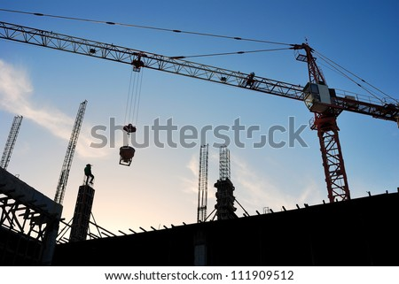 The construction crane on sunset - stock photo