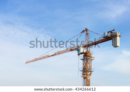 The construction crane with the blue sky,the under construction building site with the crane and blue sky.Close-up of the construction crane with the sky background.Construction crane at  work site - stock photo