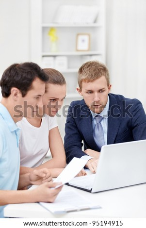 The consultant and the young couple for a laptop - stock photo