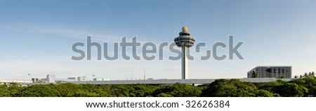 The control tower of Changi Airport in Singapore. this panoramic shows off the garden city's green trees, blue skies and cleanliness. the air traffic control tower sticks out into the sky. - stock photo