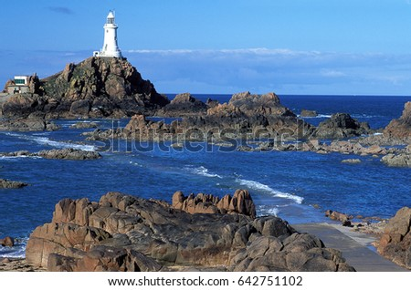 The Corbiere lighthouse on the channel island of Jersey at low tide with the formations exposed as well as sea covering the lower ground