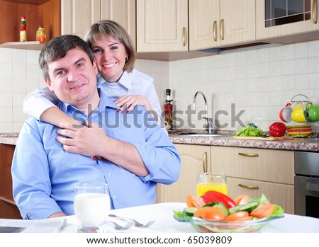 The couple has breakfast together in the kitchen - stock photo