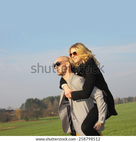 The couple has emotional and crazy fun outdoors. young beautiful couple having fun outdoors. Young happy couple outdoor portrait. - stock photo