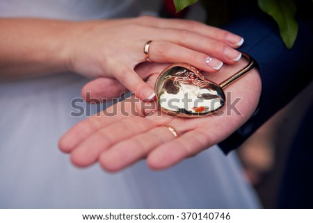 the couple holding hands in a heart-shaped lock - stock photo