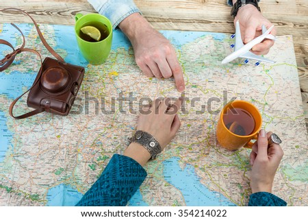 The couple is going to visit Prague, Czech Republic.  Plan your trip around the world. Top view map and hands