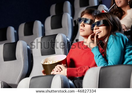The couple with pop-corn looks cinema in 3d - stock photo