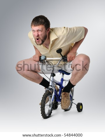 The courious man in shorts on a children's bicycle - stock photo