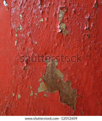 The cracked red paint on an old metallic surface. - stock photo