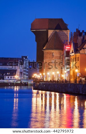 The Crane illuminated at night in Gdansk, Poland, city symbol, landmark, 15th century architecture, Motlawa River waterfront - stock photo