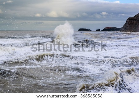 The crashing waves of a winters tide on the north coast of Great Britain from the North Sea - stock photo