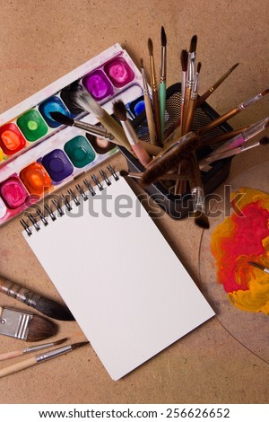 The creative process of the artist. On the table, paper, paint, apple, vase, brush - stock photo