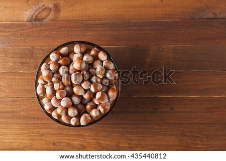 The crude hazelnut in translucent plate on the table with a wooden background with the top view, plate Is located on the left in the frame. Healthy food. - stock photo