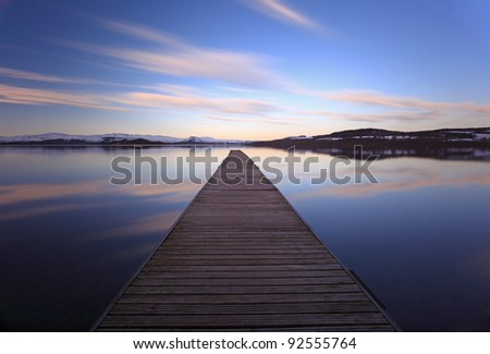 The Cruin jetty and cloud reflections. long exposure. Photographed at Duckbay marina on the west bank shores of Loch Lomond - stock photo