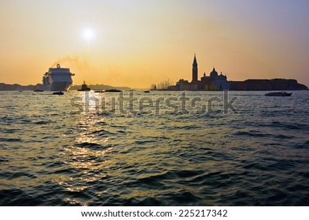 The cruise ship crosses the Venetian Lagoon at sunrise. More than 10 million tourists visit Venice every year - stock photo