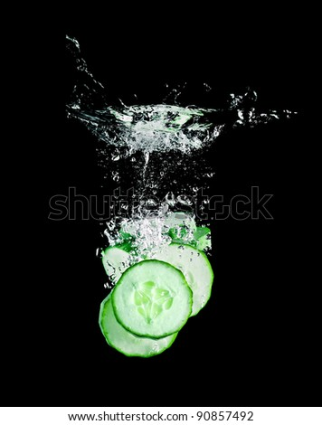 The cucumber slices falling into water . - stock photo