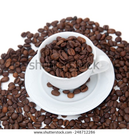 The cup of coffee beans and scattered coffee grains on white background - stock photo