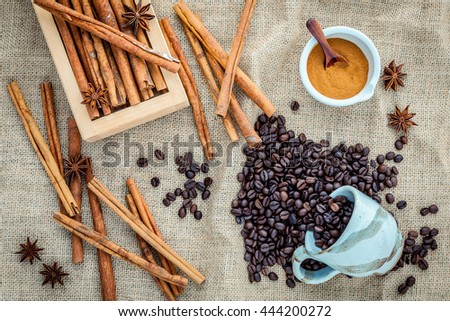 The Cup of coffee beans on the cloth sack with cinnamon sticks ,cinnamon powder in the bowl and star anise. - stock photo