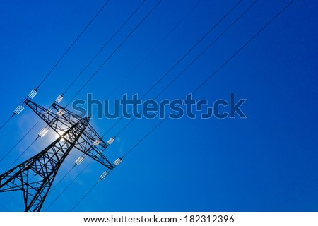 the current mast of a high voltage line with sun and blue sky. energy supply by power line. - stock photo