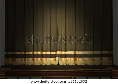The curtain on the stage in the theater with the lights off - stock photo