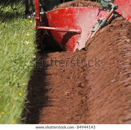 The curved mouldboard of a plough and the resulting furrow. - stock photo