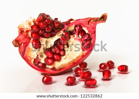 the cut pomegranate on a white background with grains - stock photo