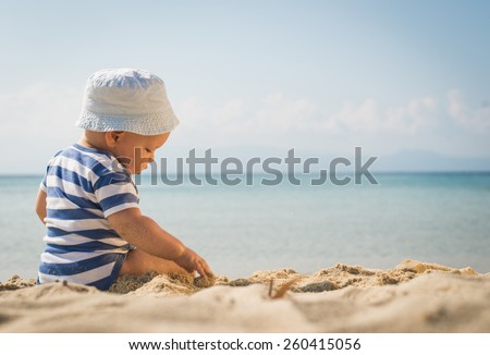 The cute baby boy playing on the beach. Little boy sitting on the sand. Sea and seashore as background. - stock photo