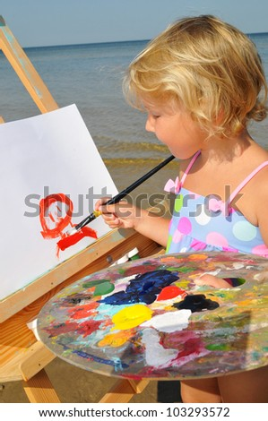The cute baby painting brush watercolors portrait on a easel - stock photo