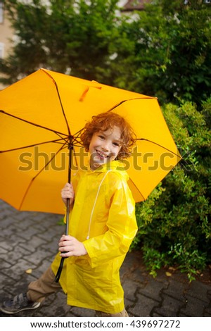 The cute boy of 8-9 years under a yellow umbrella. The boy in a bright yellow raincoat holds a big umbrella in hand. The child looks in the camera with a smile. Behind magnificent wet bush. - stock photo