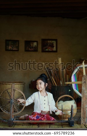 The cute girl from Chiang Mai, Thailand is   spinning cotton thread.