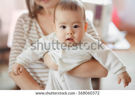 The cute little baby boy in the arms of mom on the air. Mother and infant, infant care, children and kids growing. Interestedly looks directly into the camera. - stock photo