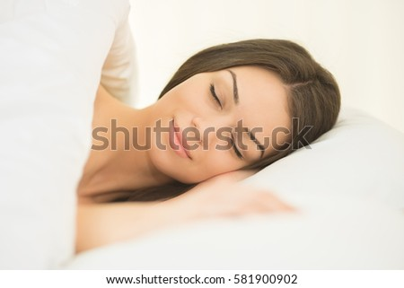 The cute woman sleeping in the white linens