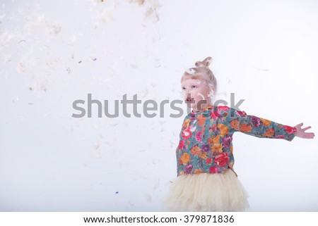 The cutest small girl posing in a white studio.